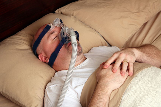 man in bed wearing full face cpap mask