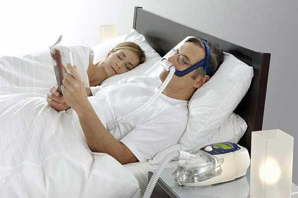 man wearing CPAP mask in bed